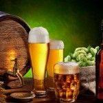 Barril de cerveza artesana rodeado de los diferentes ingredientes para elaborar cerveza casera; malta y lúpulo, vasos y botella de cerveza