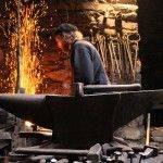 Yunque en primer término con martillo y clavos, de fondo herrero Friedric Bramsteidl trabajando en la fragua, con llamas de fuego altas y mazo de fondo