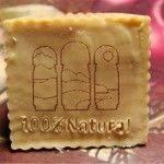 Jabón con logotipo grabado de Asturias Paraiso natural y la palabra 100% natural sobre un fondo de madera con dos rosas pintadas