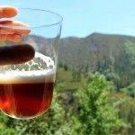 mano sujetando vaso de sidra con cerveza casera con color ambar elaborada con malta chocolate y malta Ale. Paisaje de montañas de fondo
