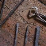 tenazas, punzones y cinceles para trabajar el hierro sobre un fondo de madera antigua